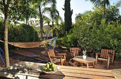 צימר באיזור הצפון | בקתות הלוטם - שטח חוץ פרטי הכולל שולחן פיקניק, ערסל ונדנדת עץ מפנקים