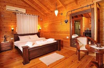 צימר באיזור הצפון | בקתות הלוטם - מיטת עץ המתהדרת עם גופי תאורה מיוחדים לאווירה רומנטית